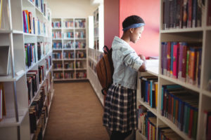 rsz attentive schoolgirl reading book in library c6msdz7