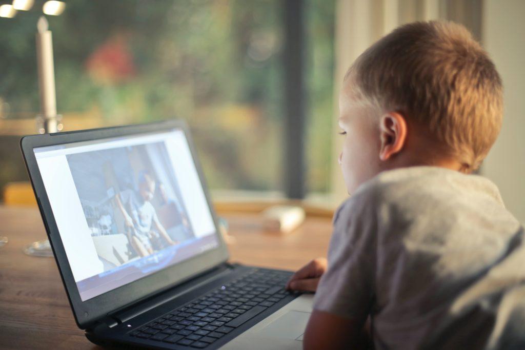 boy watching video using laptop 821948